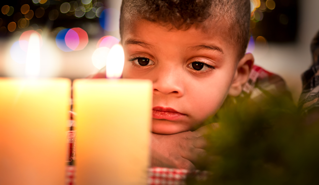 Young boy looks at holiday candles