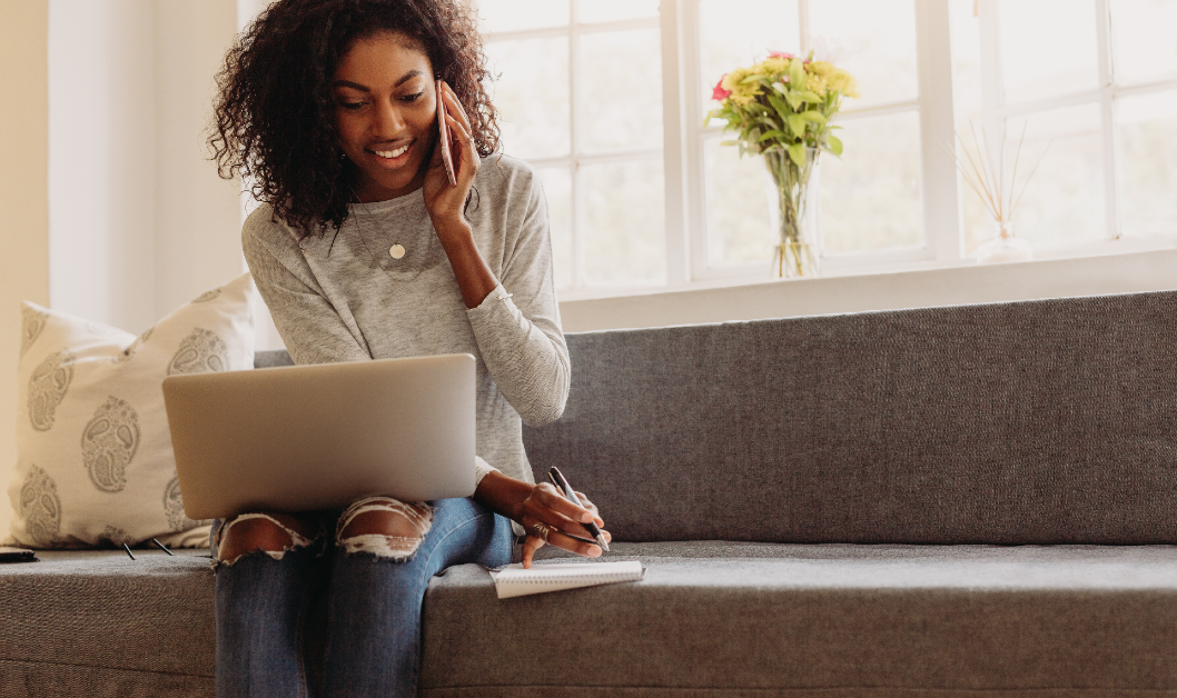 Woman on laptop and talking on cellphone while sitting on couch