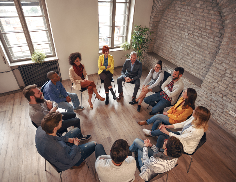 Group of diverse people sitting in a circle talking